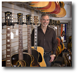 Gary Standing with Large Inventory of Vintage Guitars